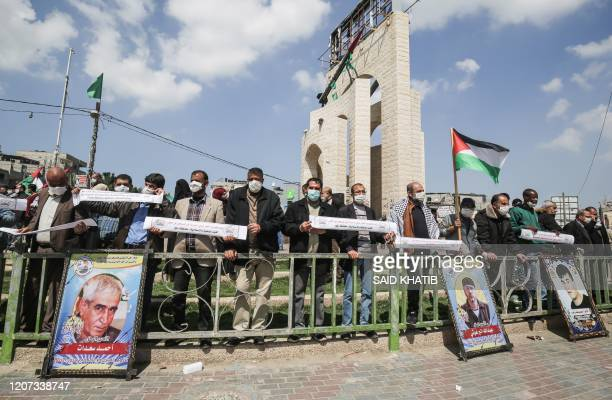 Palestinians, wearing protective masks amid fears of the spread of the novel coronavirus, and waving national flags take part in a protest in...