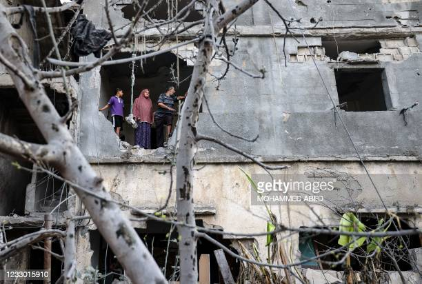 Palestinians who have returned to their neighbourhood, assess the damage in their home hit by Israeli bombardment in Gaza City, after a ceasefire...