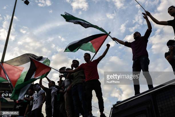 Palestinians who live in Greece wave Palestinian flags at the top of police bus during a protest against the bloodshed along the Gaza border and...