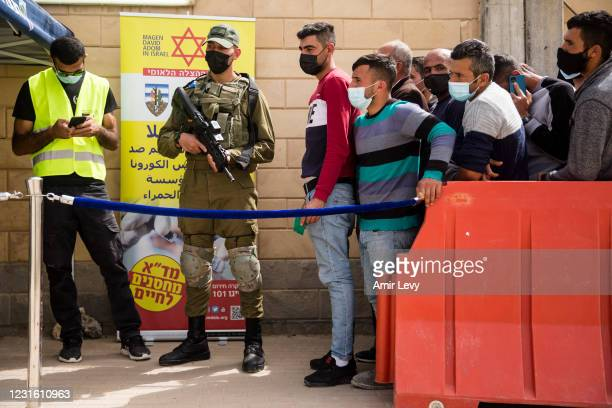 Palestinians who work in Israel wait in line to receive the first dose of a Moderna Covid-19 vaccine by Israeli medical workers in Meitar crossing...