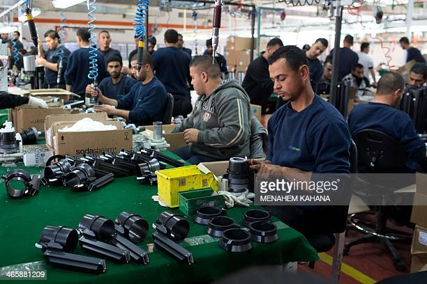 Palestinians work at the Israeli SodaStream factory in the Mishor Adumim industrial park next to the West Bank settlement of Maale Adumim on January...