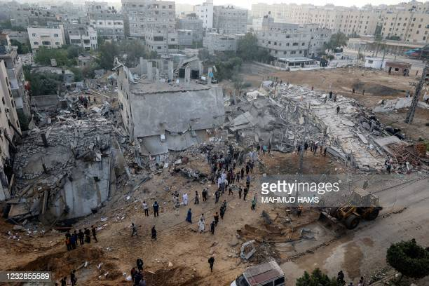 Palestinias check the damage as they gather next to destroyed buildings on the first day of the Muslim Eid al-Fitr holiday, which marks the end of...