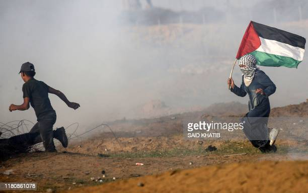 Palestinin woman waving a national flag and a boy run from tear gas fired by Israeli troops during clashes following a demonstration along the border...