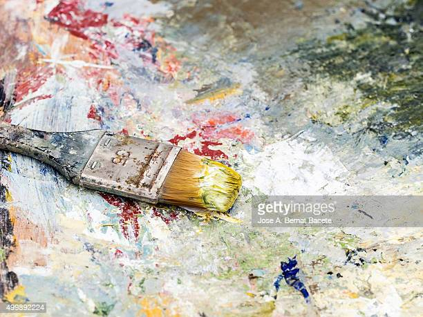 Palette of a painter with colors of oil paints and a paintbrush