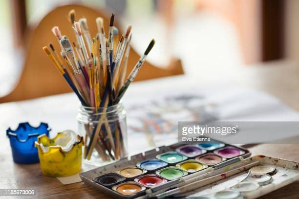 palette of compact paints and a glass jar full of paintbrushes on a dining table - ええじゃないか 発祥の地 ストックフォトと画像