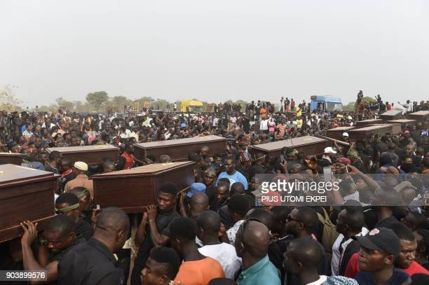 Pall bearers carry coffins during the funeral service for people killed during clashes between cattle herders and farmers, on January 11 in Ibrahim...