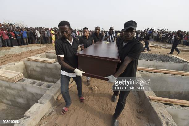 Pall bearers carry coffins during the funeral service for people killed during clashes between cattle herders and farmers on January 11 in Ibrahim...