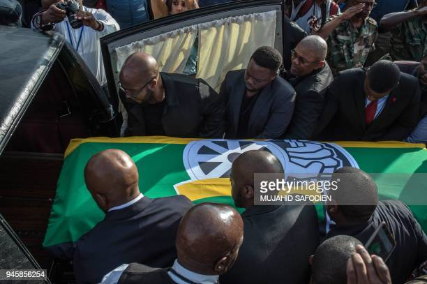 Pall bearers carry the casket of Winnie MadikizelaMandela covered with an ANC flag as remains of the the antiapartheid icon are returned to her home...
