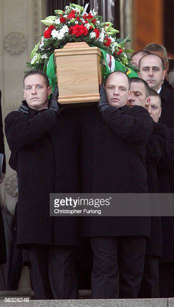 Pall bearers carry the coffin of footballer George Best as it makes its way from the service at Stormont Parliament buildings Great Hall to Roselawn...