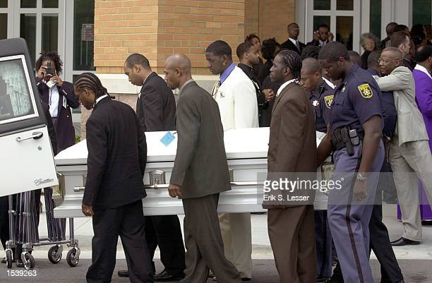 Pall bearers place the coffin containing the body of Lisa Left Eye Lopes into a hearse at the conclusion of the public funeral for the TLC singer at...