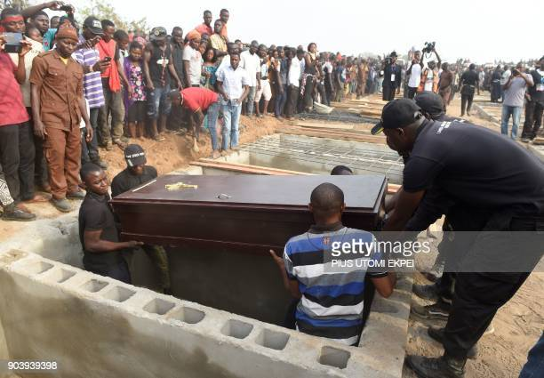 Pall bearers put a coffin in a grave during a mass burial for 73 persons who died following clashes between Fulani herdsmen and natives of Guma and...