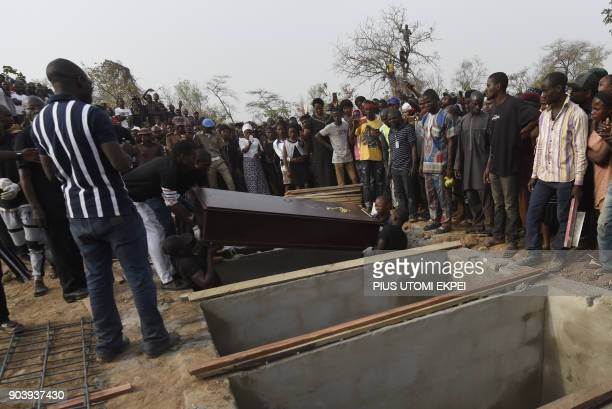Pall bearers put coffin in a grave during a mass burial for 73 persons who died following clashes between Fulani herdsmen and natives of Guma and...