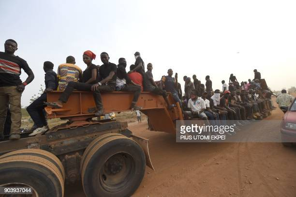 Pall bearers ride in open truck after a funeral service and mass burial for 73 persons who died following clashes between Fulani herdsmen and natives...