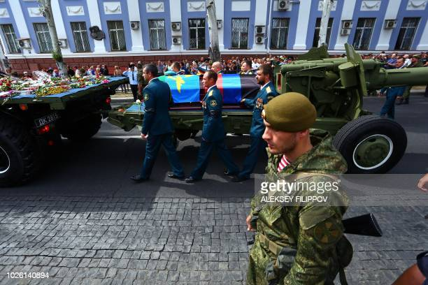 Pall bearers walk with the coffin displayed on a piece of heavy artillery during the funeral ceremony for assassinated leader of the selfproclaimed...