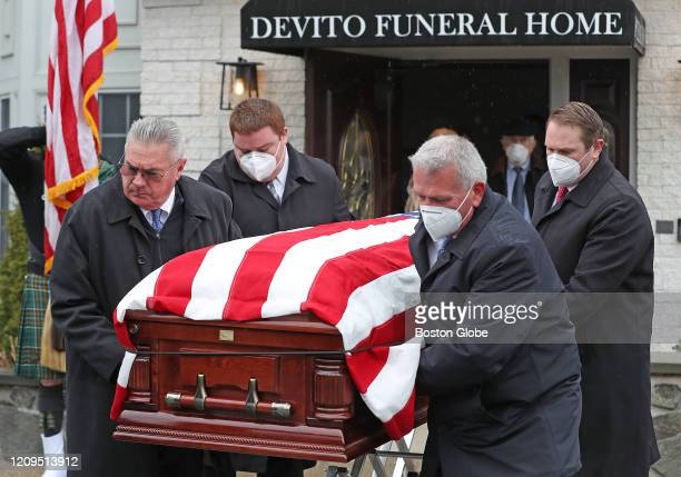 Pall bearers wear protective masks while carrying a flagdraped casket at a memorial parade for Air Force nurse Mary T Foley who died without kin in...