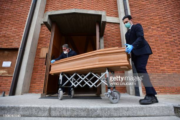Pallbearers bring the coffin of deceased person to be stored into the church of San Giuseppe in Seriate, near Bergamo, Lombardy, on March 26 during...