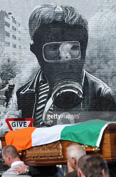 Pallbearers carry a coffin draped with a republican flag during a funeral procession moments before the march by relatives of Bloody Sunday victims...