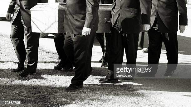 pallbearers carry coffin to cemetery plot - pallbearer stock photos and pictures