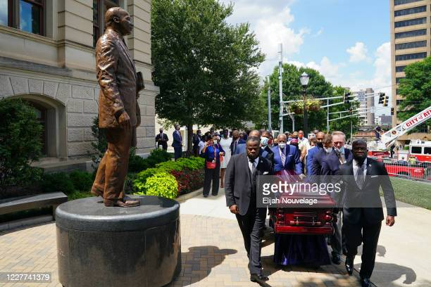 Pallbearers carry the body of civil rights leader C.T. Vivian past a statue of Dr. Martin Luther King Jr. At the Georgia Capitol building on July 22,...