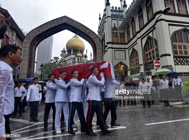 Pallbearers carry the casket draped with state flag of late Othman Wok a member of independent Singapore's first Cabinet from Masjid Sultan after a...