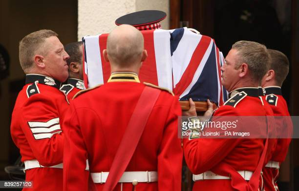 Pallbearers carry the coffin of Lance Sergeant Dale McCallum of 1st Battalion Scots Guards into the New Testament Church of God in Willesden north...