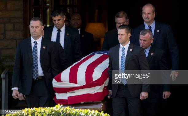 Pallbearers carry the flagdraped casket of the remains of President George HW Bush into the hearse during the first departure ceremony at George H...