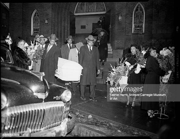 Pallbearers carrying light colored casket out of Wesley Center AME Zion Church for funeral of Elizabeth Harper wife of Walt Harper surrounded by...