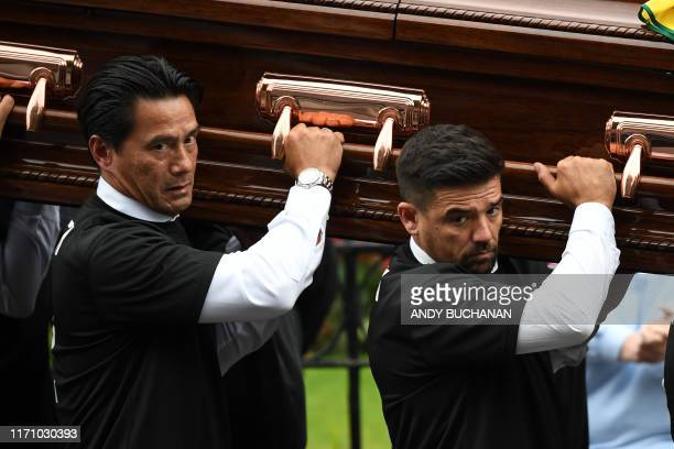 Pallbearers including Retired Dutch footballer Michael Mols and Spain's former footballer Nacho Novo wearing a number 2 shirt with the name of...