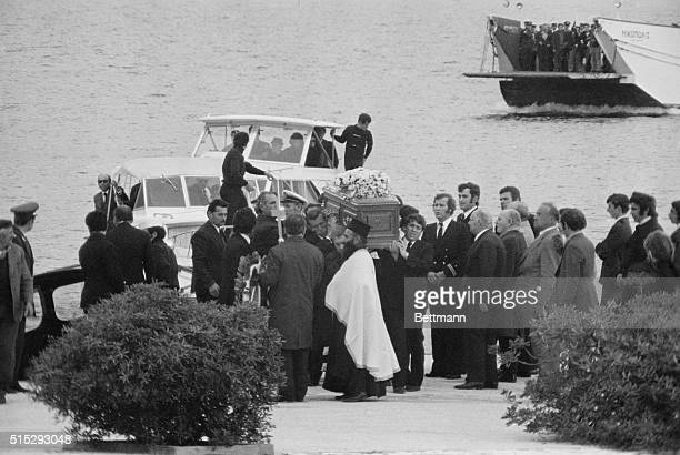 Pallbearers lift the coffin containing the body of Aristotle Onassis from a launch as a ferry with the family members arrives on the Greek...