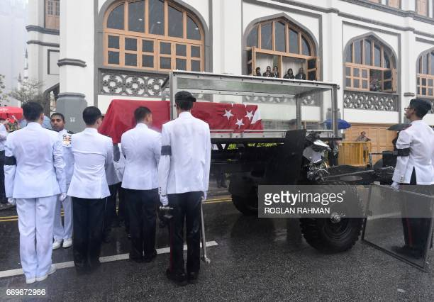 Pallbearers load the casket draped with state flag of late Othman Wok a member of independent Singapore's first Cabinet to the gun carriage from...