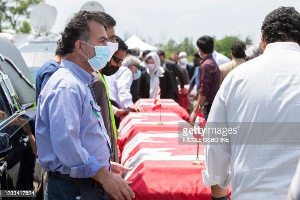 Pallbearers move the caskets of four members of the Afzaal Family at the Islamic Centre of Southwest Ontario on June 12 during the funeral service,...