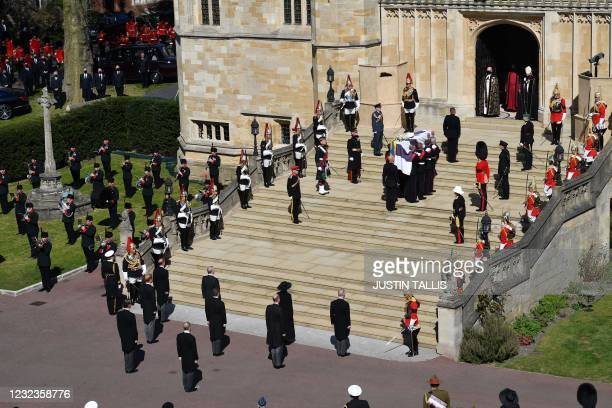 Pallbearers of the Royal Marines carrying the coffin and members of the Royal family pause for a minute's silence at the West Steps of St George's...