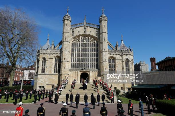 Pallbearers of the Royal Marines carrying the coffin and members of the armed forces pause for a minute's silence at the West Steps of St George's...