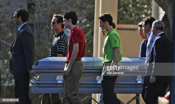 Pallbearers walk the casket of Scott Beigel, a teacher at Marjory Stoneman Douglas High School who was killed in the mass shooting, to his final...