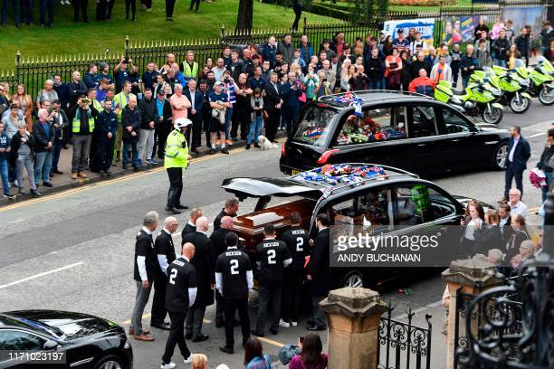 TOPSHOT Pallbearers wearing a number 2 shirt with the name of Fernando Ricksen written on them prepare to carry the coffin of Rangers Dutch former...