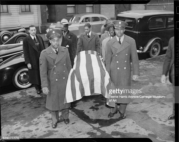 Pallbearers wearing US Army uniform double breasted overcoats holding flag draped casket on sidewalk with cars parked in street in background circa...