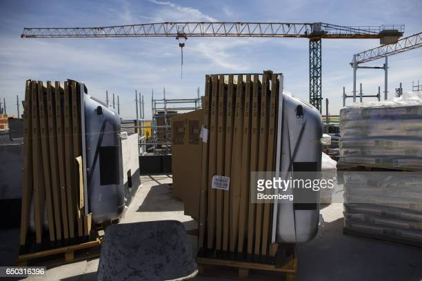 Pallets containing stacks of new metal bathtubs sit among building supplies at a residential construction site operated by Neinor Homes SLU in the...