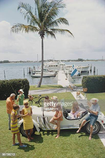 Palm Beach socialite Jim Kimberly and friends around his white sports car on the shores of Lake Worth Florida April 1968