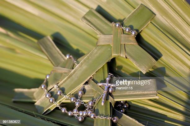 Palm crosses and rosary beads on palm leaves
