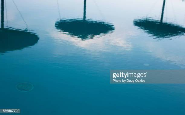 Palm Frond Umbrellas are Seen in Reflection on the surface of a Greek hotel pool in Santorini
