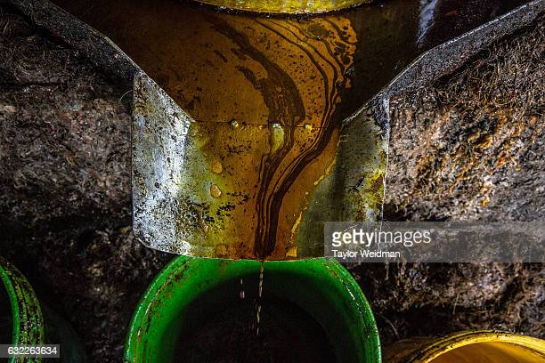 Palm oil drips into a bucket after being pressed in an oil mill at Asia World on November 11 2016 in Bank Mae Village Myanmar The oil is sent to...