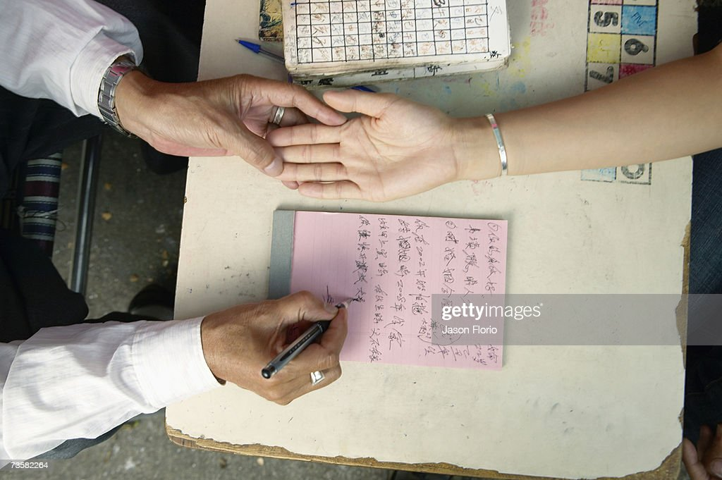 Palm reader taking notes on woman's hand : Stock Photo