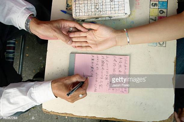 Palm reader taking notes on woman's hand