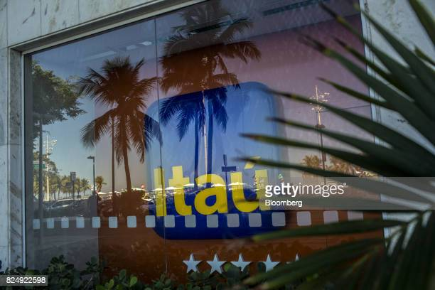 Palm streets are seen reflected in the window of an Itau Unibanco SA bank branch in Rio de Janeiro Brazil on Monday July 31 2017 Itau Unibanco SA is...