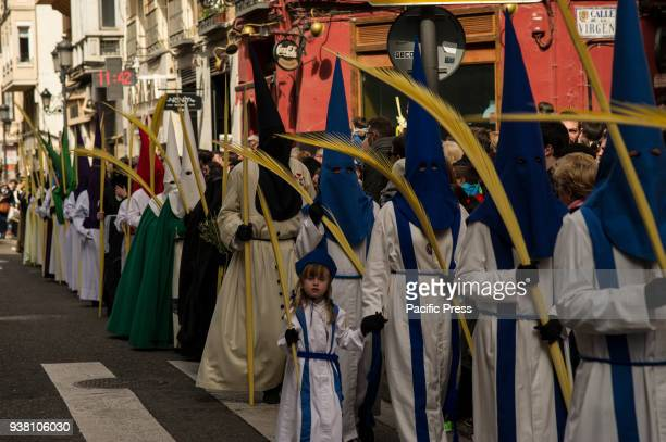 Palm Sunday marks the beginning of the Holy Week in the Christian calendar seven days of passion and devotion Masked penitents in procession on Palm...