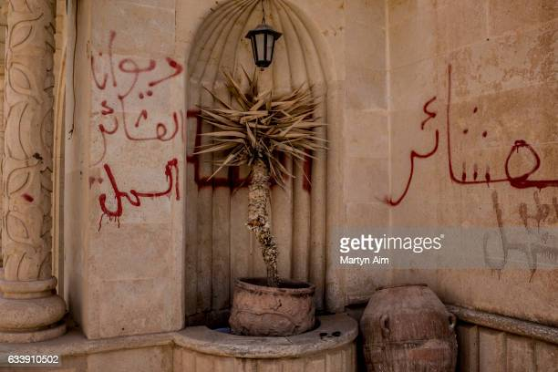 Palm tree and ancient urn with walls covered in graffiti written by Islamic State militants in the Mar Behnam monastery on February 4, 2017 in Beth...