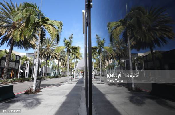 Palm trees are reflected in a shuttered store window along iconic and nearly empty Rodeo Drive on March 18, 2020 in Beverly Hills, California. The...