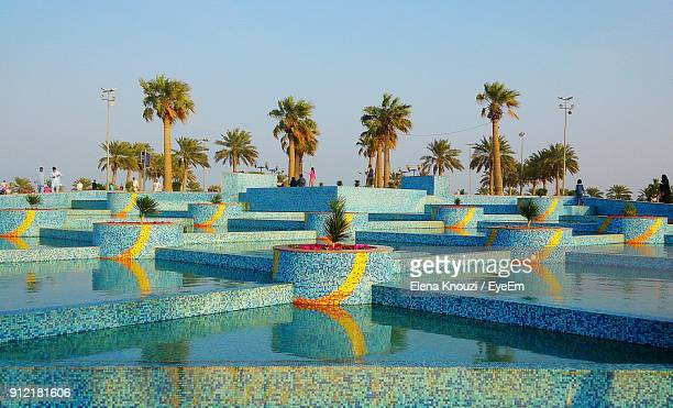 palm trees by swimming pool against sky - elena knouzi stock pictures, royalty-free photos & images