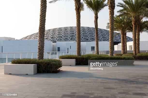 Palm trees line an avenue near the Louvre Abu Dhabi museum on Saadiyat Island in Abu Dhabi, United Arab Emirates, on Wednesday, Oct. 2, 2019. Abu...