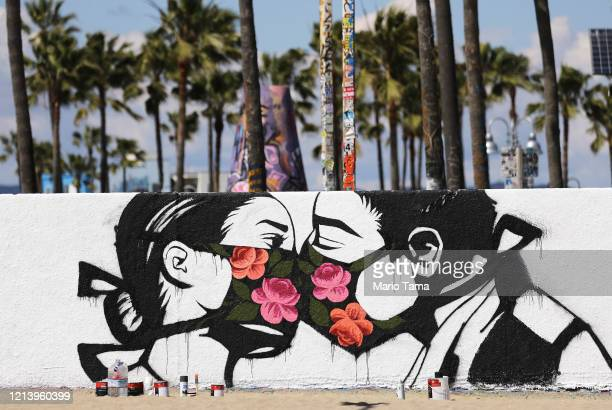 Palm trees stand behind a street art piece by artist Pony Wave depicting two people kissing while wearing face masks on Venice Beach on March 21,...
